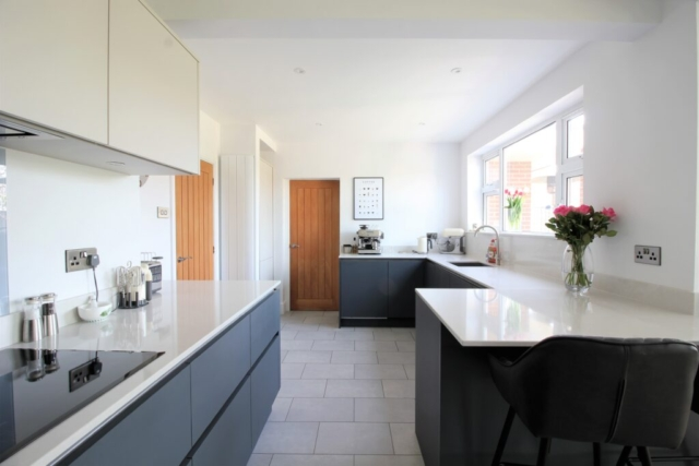 This modern Masterclass H-Line kitchen in Keyworth Nottinghamshire was created by Owen Williams Kitchens based in Coalville. Our true handleless Sutton range was fitted with 'Heather Slate' on the base cabinets and 'Highland Stone' on the wall cabinets to add a little warmth.  We teamed these with a titanium finish on the handle rails, 'Desert Silver' Silestone worktops and Bosch built-in appliances.